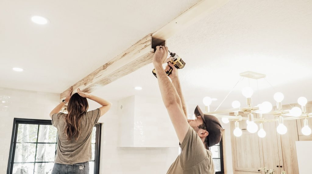 Installing Faux Wood Beams on Your Ceiling: Screwing the beam in